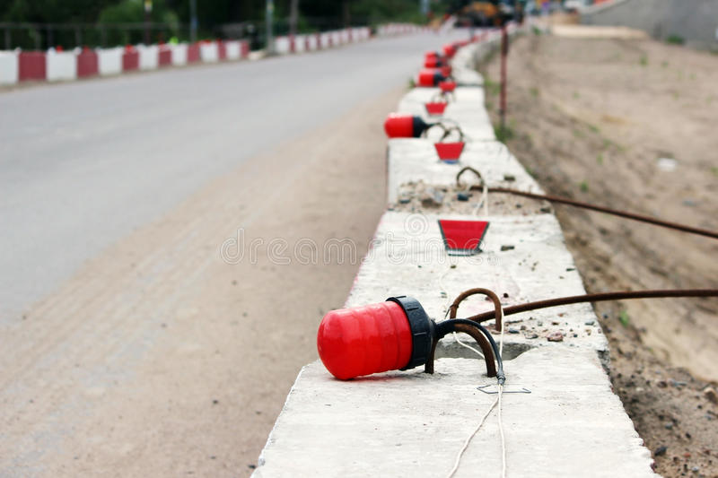 Signal lights on the fundamental blocks of concrete, fencing construction the viaduct from the existing road. Signal lights on the fundamental blocks of royalty free stock photos