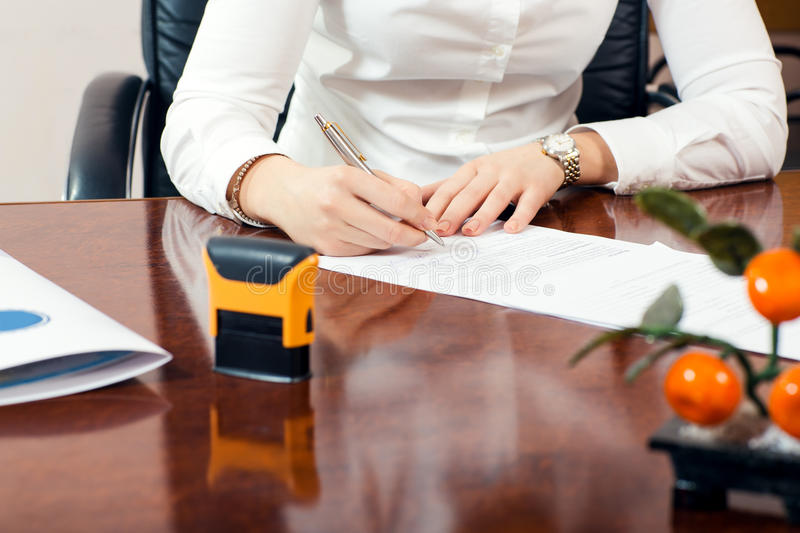 Signature document. Businesswoman signature document, working at her office royalty free stock images