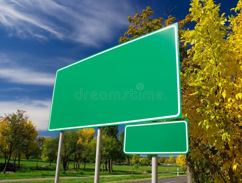 Signboard. Empty green signboard at the roadside in an autumn landscape. Add your own text stock photo