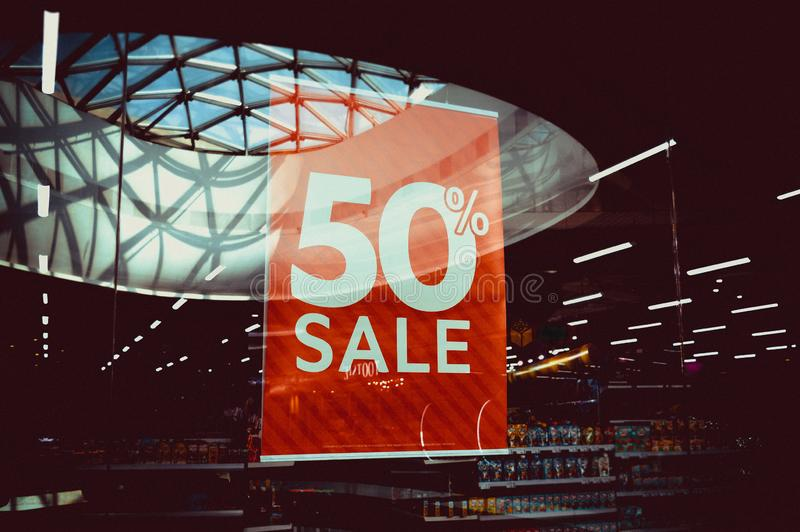 Signboard with the inscription Sale 50 in the fashion store. Image of a sale ad in a clothing store window stock photography