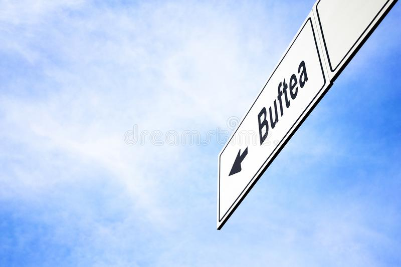 Signboard pointing towards Buftea. White signboard with an arrow pointing left towards Buftea, Romania, against a hazy blue sky in a concept of travel stock photo