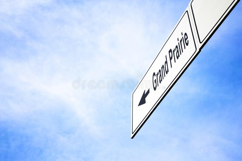 Signboard pointing towards Grand Prairie. White signboard with an arrow pointing left towards Grand Prairie, Texas, USA, against a hazy blue sky in a concept of stock photography