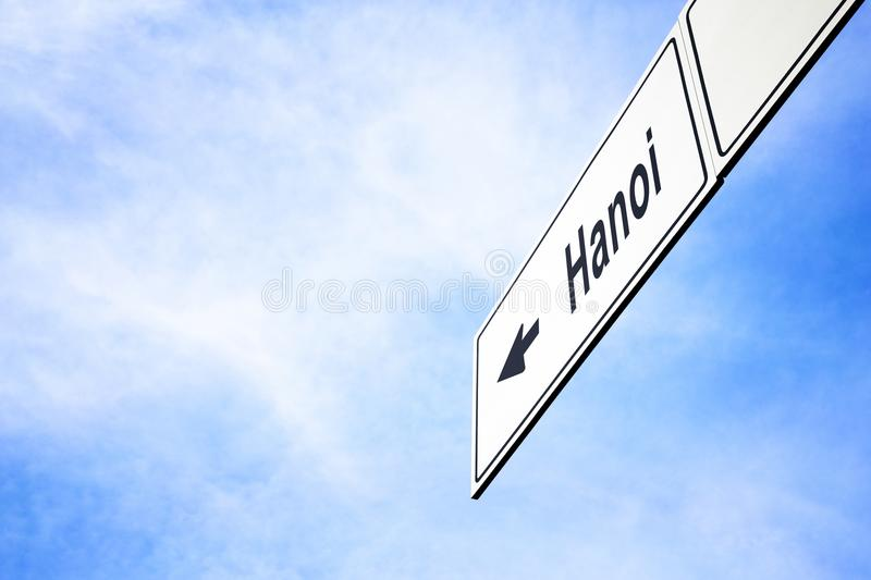 Signboard pointing towards Hanoi. White signboard with an arrow pointing left towards Hanoi, Vietnam, against a hazy blue sky in a concept of travel, navigation stock image