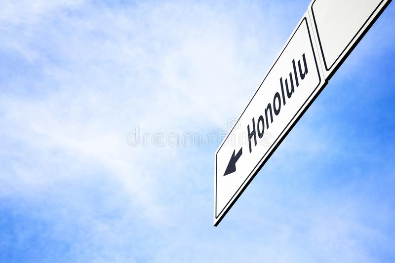 Signboard pointing towards Honolulu. White signboard with an arrow pointing left towards Honolulu, Hawai, USA, against a hazy blue sky in a concept of travel stock photography