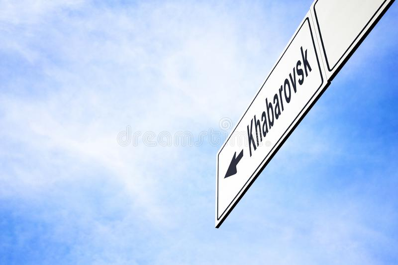 Signboard pointing towards Khabarovsk. White signboard with an arrow pointing left towards Khabarovsk, Khabarovsk Krai, Russia, against a hazy blue sky in a royalty free stock photos