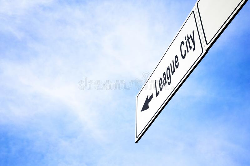 Signboard pointing towards League City. White signboard with an arrow pointing left towards League City, Texas, USA, against a hazy blue sky in a concept of stock photos