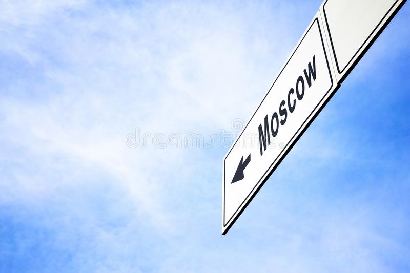 Signboard pointing towards Moscow. White signboard with an arrow pointing left towards Moscow, Russia, against a hazy blue sky in a concept of travel, navigation stock photos
