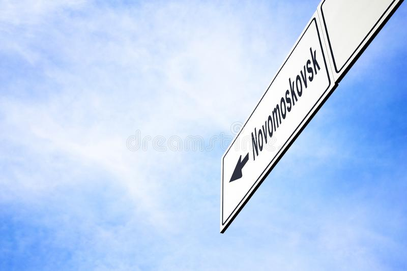 Signboard pointing towards Novomoskovsk. White signboard with an arrow pointing left towards Novomoskovsk, Tula Oblast, Russia, against a hazy blue sky in a stock images