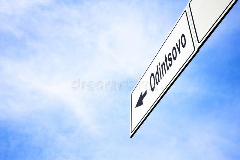 Signboard pointing towards Odintsovo. White signboard with an arrow pointing left towards Odintsovo, Moscow Oblast, Russia, against a hazy blue sky in a concept stock photo