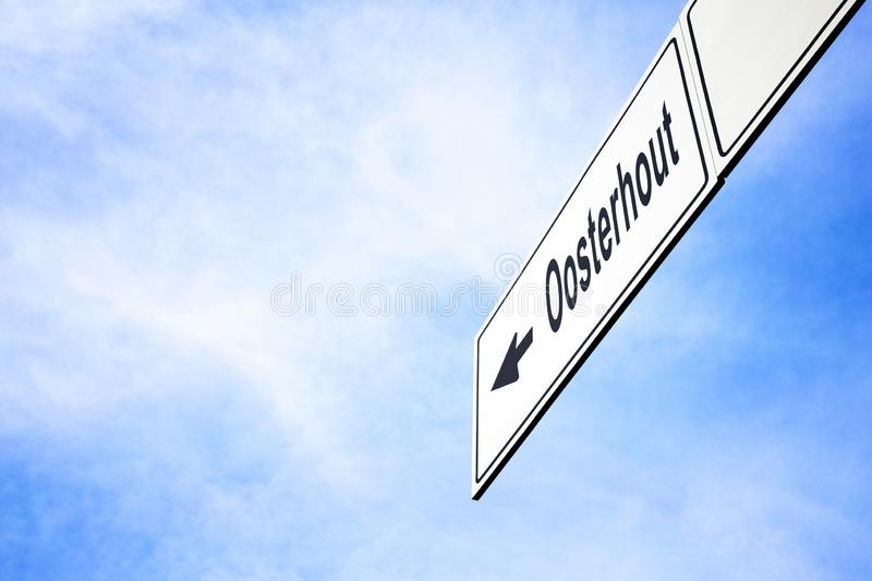 Signboard pointing towards Oosterhout. White signboard with an arrow pointing left towards Oosterhout, Netherlands, against a hazy blue sky in a concept of stock photos