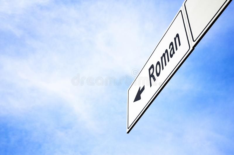 Signboard pointing towards Roman. White signboard with an arrow pointing left towards Roman, Romania, against a hazy blue sky in a concept of travel, navigation stock images