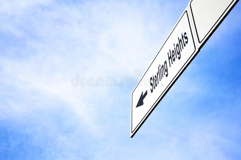 Signboard pointing towards Sterling Heights. White signboard with an arrow pointing left towards Sterling Heights, Michigan, USA, against a hazy blue sky in a stock photography