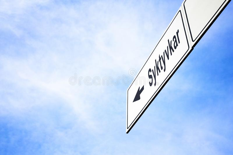 Signboard pointing towards Syktyvkar. White signboard with an arrow pointing left towards Syktyvkar, Komi Republic, Russia, against a hazy blue sky in a concept stock image