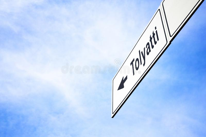 Signboard pointing towards Tolyatti. White signboard with an arrow pointing left towards Tolyatti, Samara Oblast, Russia, against a hazy blue sky in a concept of royalty free stock image