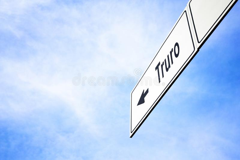 Signboard pointing towards Truro. White signboard with an arrow pointing left towards Truro, England, United Kingdom, against a hazy blue sky in a concept of stock photo