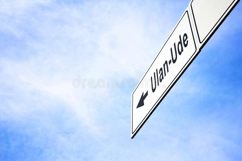 Signboard pointing towards Ulan-Ude. White signboard with an arrow pointing left towards Ulan-Ude, Republic of Buryatia, Russia, against a hazy blue sky in a stock photography