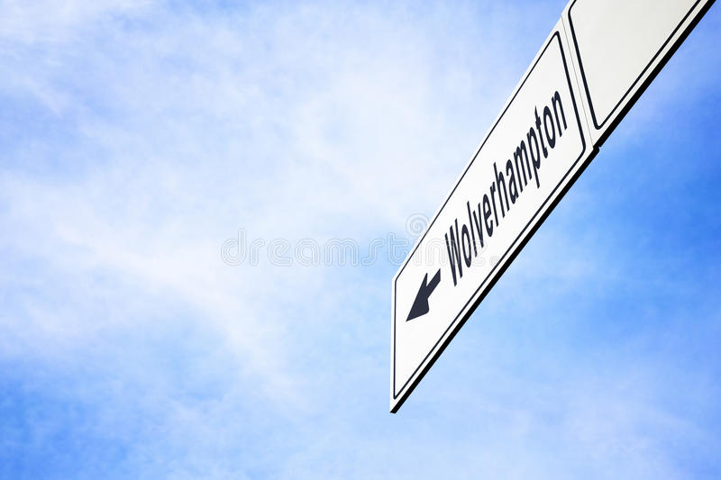 Signboard pointing towards Wolverhampton. White signboard with an arrow pointing left towards Wolverhampton, England, United Kingdom, against a hazy blue sky in stock image