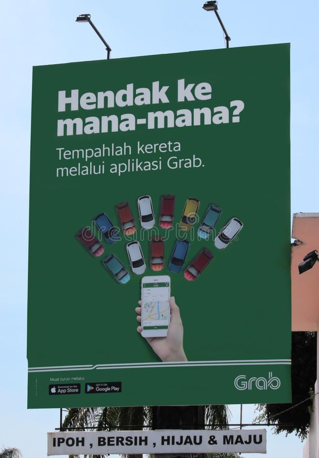 Billboard Promoting The Smartphone App By Grab. An advertising signboard in the Malay language promoting the ride-hailing smartphone app on Apple`s IOS and royalty free stock photos