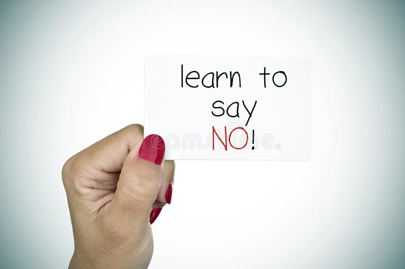 Signboard with the text learn to say no. Closeup of the hand of a young woman with red polished nails holding a signboard with the text learn to say no stock photo