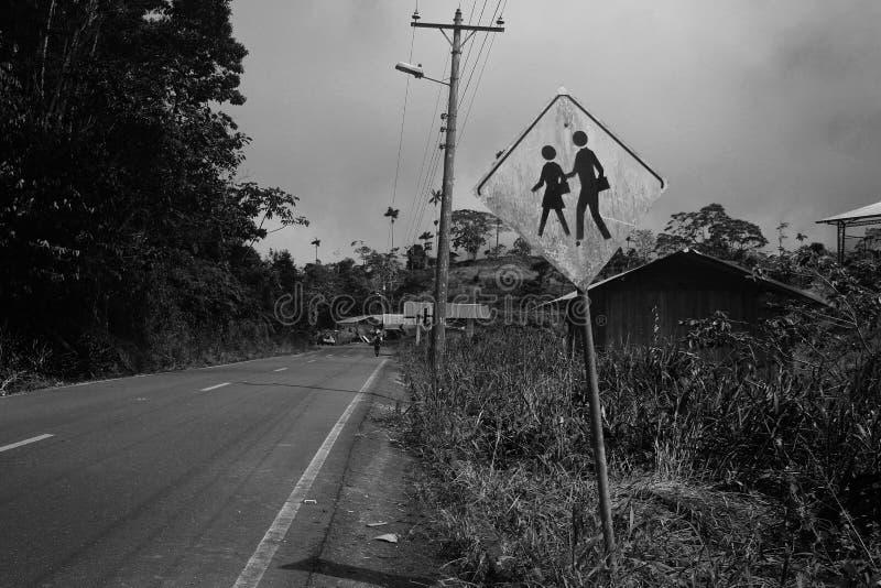 Signe ? c?t? de route dans un village indiquant qu'il y a une ?cole et des enfants actuels dans le blanc noir images libres de droits