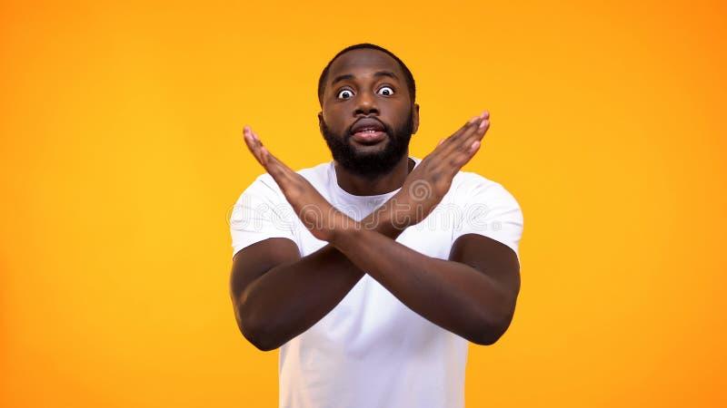 Signe afro-américain d'arrêt d'apparence de jeune homme à la main sur le fond jaune, avertissement photo stock