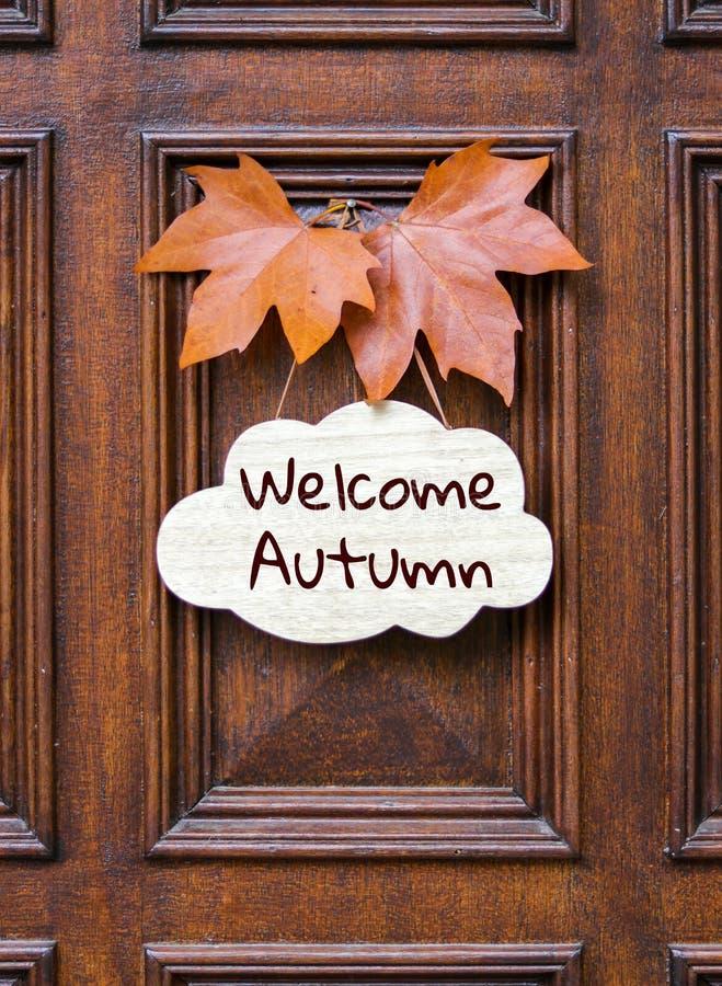 Signe avec l'automne bienvenu de mots de lettrage décoré de deux feuilles d'érable d'orange accrochant sur la porte d'entrée en b image stock