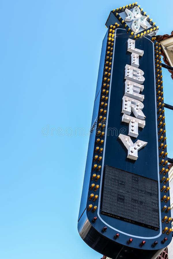 Signe bleu-foncé avec les lettres blanches/marquant avec des lettres la LIBERTÉ et les ampoules pour illuminer la nuit images libres de droits