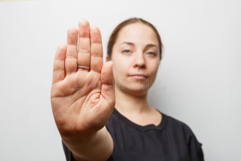 Signe d'ARRÊT d'apparence de fille ou AUCUN geste à la main, foyer sur la paume photographie stock libre de droits