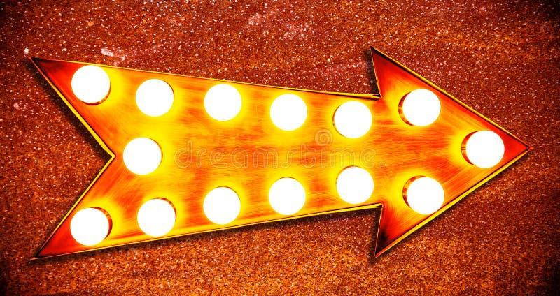 Signe d'or lumineux lumineux et coloré de vintage orange, jaune et rougeâtre de couleur d'affichage métallique de flèche avec les photos stock