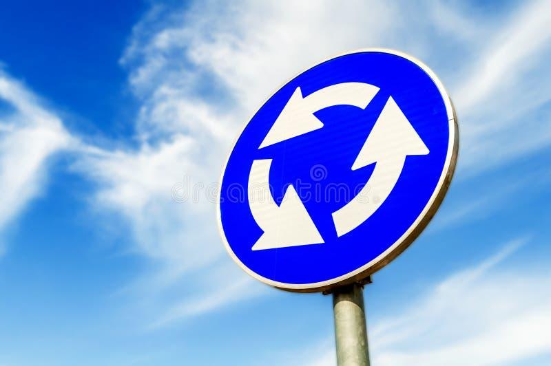 Signe de circulation routière bleu de carrefour de rond point contre le ciel bleu photo libre de droits