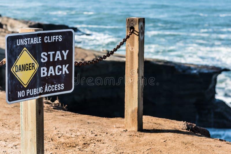 Signe de danger avec la balustrade aux falaises de coucher du soleil images libres de droits