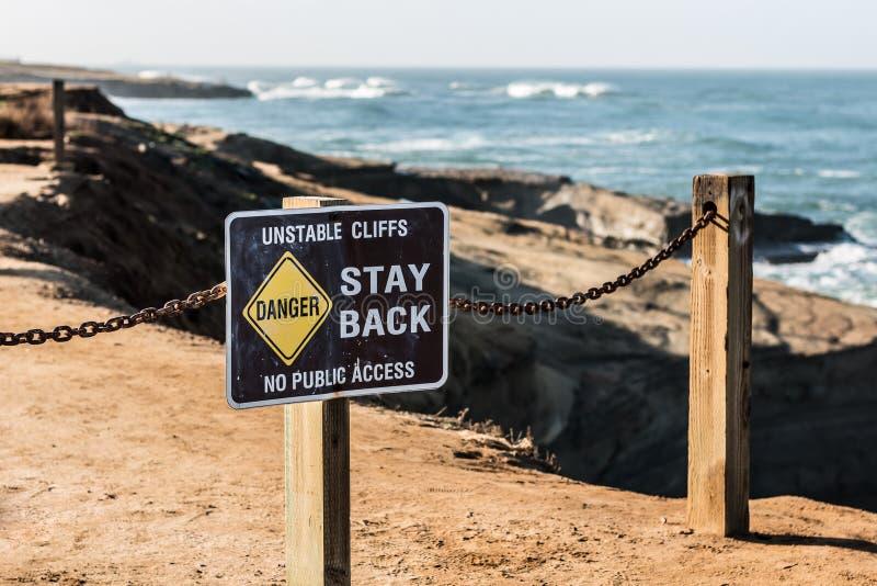 Signe de danger avec la clôture aux falaises de coucher du soleil image libre de droits