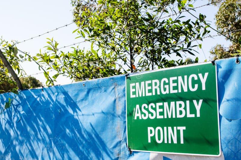 Signe de l'information pour le point d'assemblée de secours attaché sur l'entrée du chantier de construction images stock
