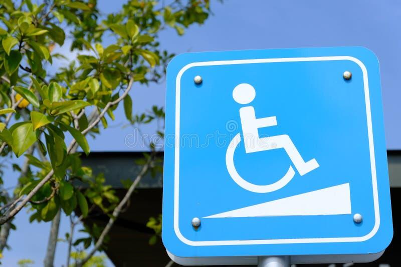 Signe de manière de pente pour des personnes de fauteuil roulant sur le fond de ciel bleu - stationnement handicapé image stock