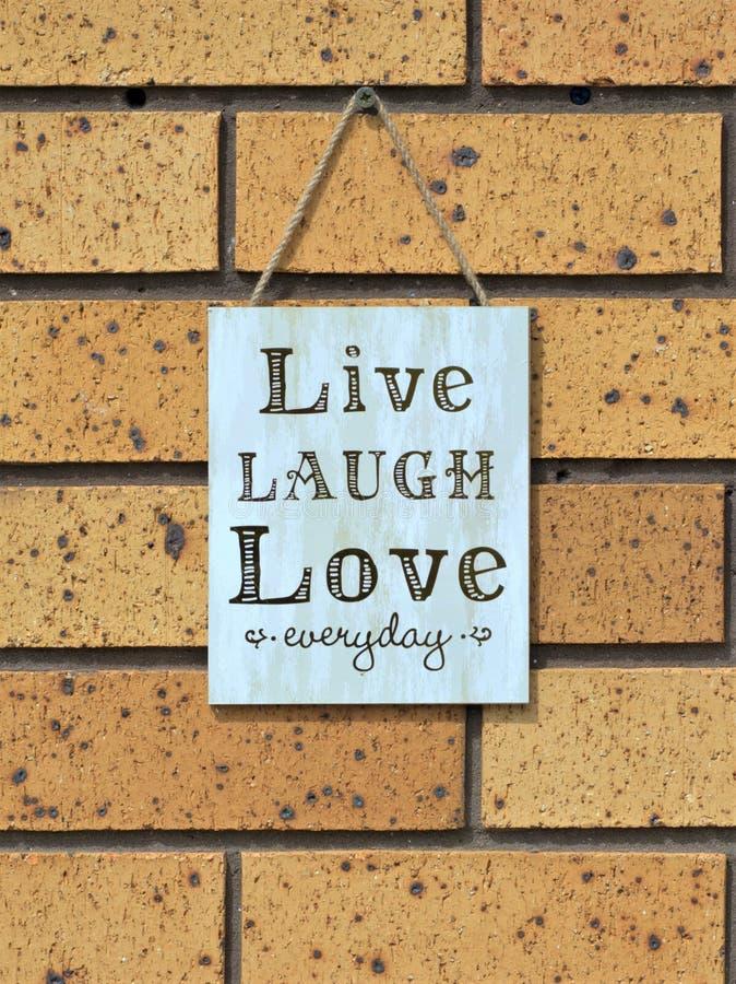 Signe de mur indiquant le ` quotidien d'amour vivant de rire de ` photographie stock libre de droits