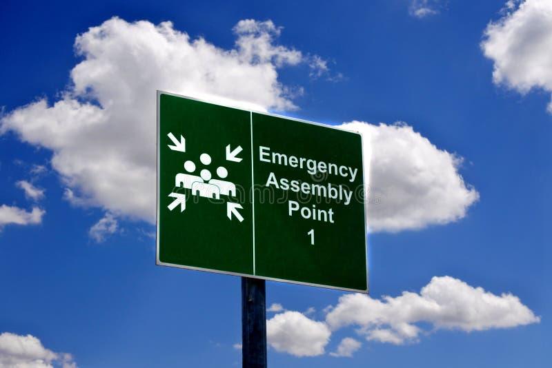 Signe de point d'assemblée de secours contre le ciel bleu photo stock