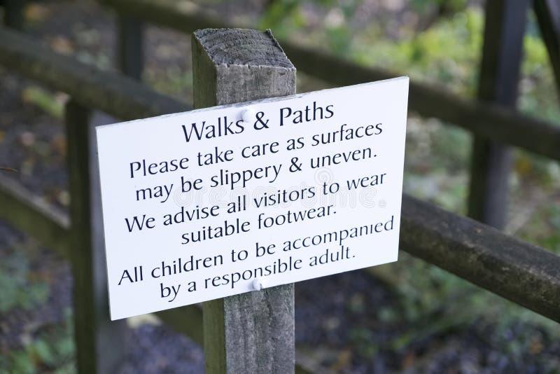 Signe de sécurité de promenades et de chemins pour que les marcheurs portent le risque approprié approprié de chaussures de voyag image libre de droits