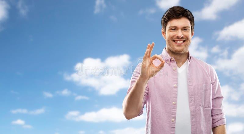 Signe de sourire de main d'ok d'apparence de jeune homme au-dessus de ciel photo libre de droits