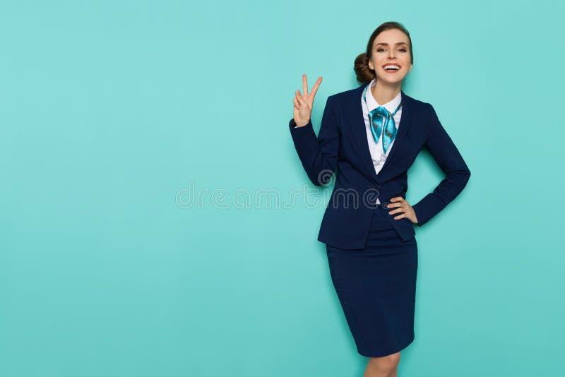 Signe de sourire de main d'Is Showing Peace d'hôtesse photographie stock libre de droits