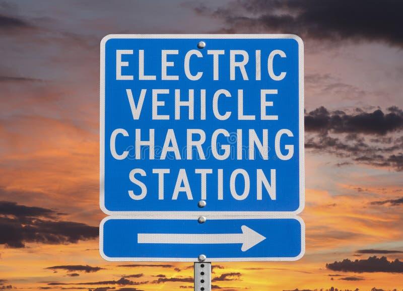 Signe de station de charge de véhicule électrique avec le ciel de coucher du soleil image libre de droits