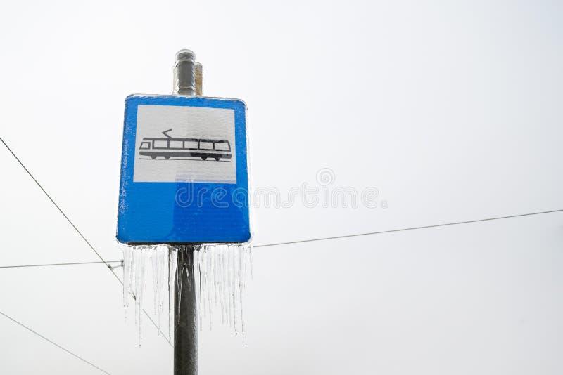Signe de station de tram avec des glaçons pendant de lui, sur le fond bleu, pendant l'hiver, avec un ciel obscurci dans le dos images stock