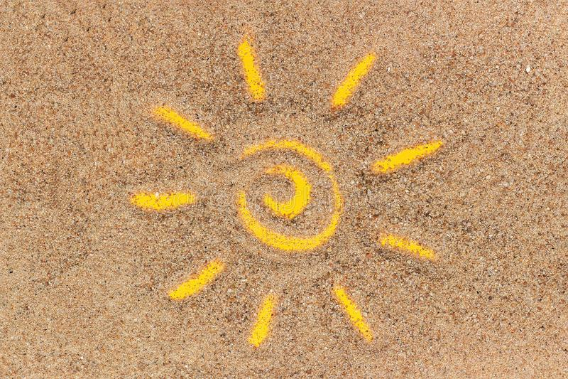 Signe de Sun dessiné sur le sable et le tube blanc de la protection solaire Maquette de calibre pour votre conception Vue supérie images stock