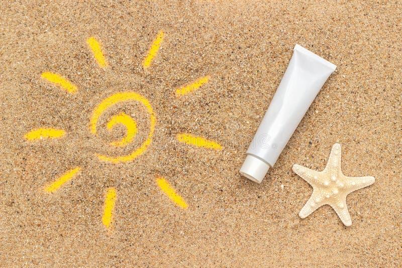Signe de Sun dessiné sur le sable, les étoiles de mer et le tube blanc de la protection solaire Maquette de calibre pour votre co images libres de droits