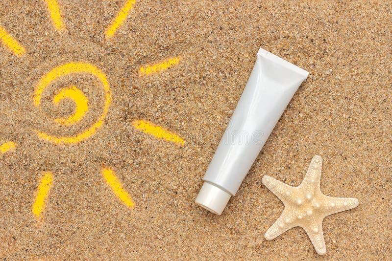 Signe de Sun dessiné sur le sable, les étoiles de mer et le tube blanc de la protection solaire, plan rapproché Maquette de calib image libre de droits