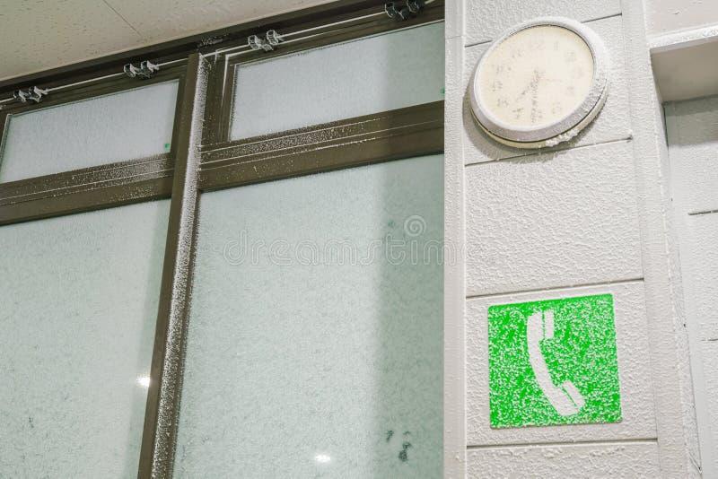 Signe de téléphone public couvert de neige image stock