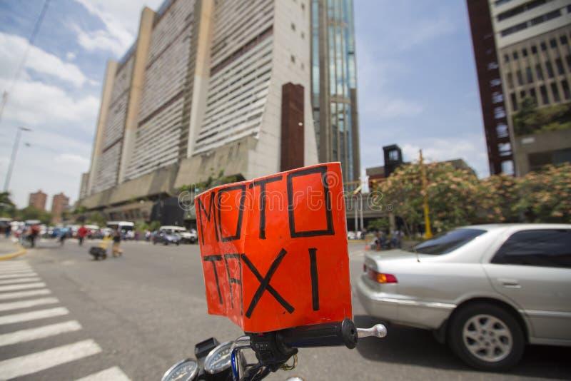 Signe de taxi de Moto se tenant sur une motocyclette, Caracas images libres de droits