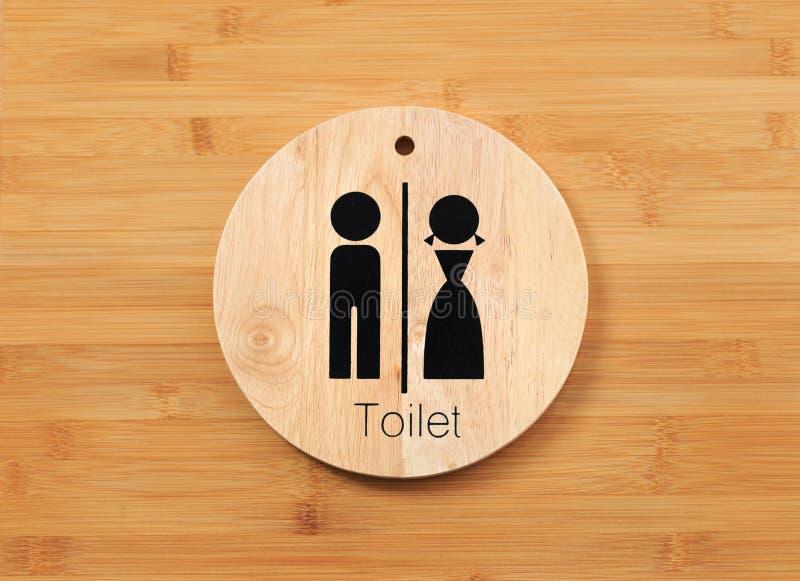 Signe de toilette de masculin et de femelle sur le bois naturel pour des toilettes avec le fond de panneau de porte de bois dur photo libre de droits