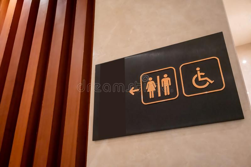 Signe de toilettes fait de métal d'or sur le conseil noir accrochant sur le mur photo libre de droits