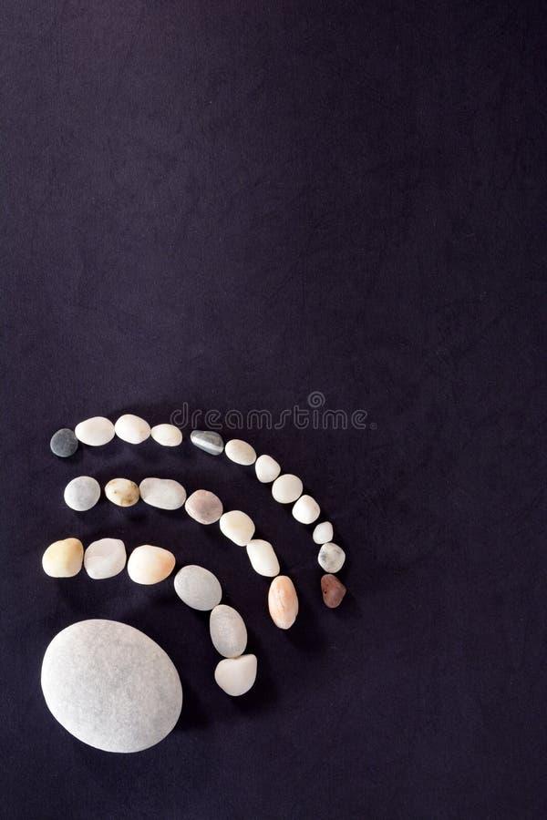 Signe de WI fi présenté des pierres de mer sur un fond foncé images libres de droits