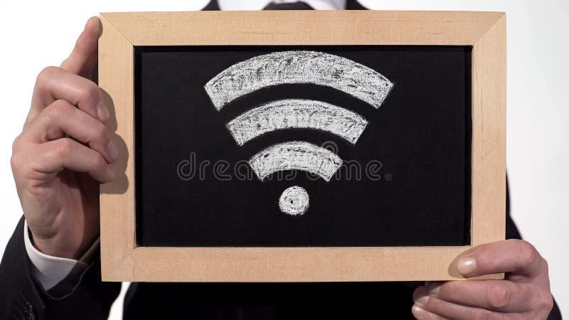 Signe de zone de Wi-Fi dessiné sur le tableau noir dans des mains d'homme d'affaires, technologie d'Internet image libre de droits